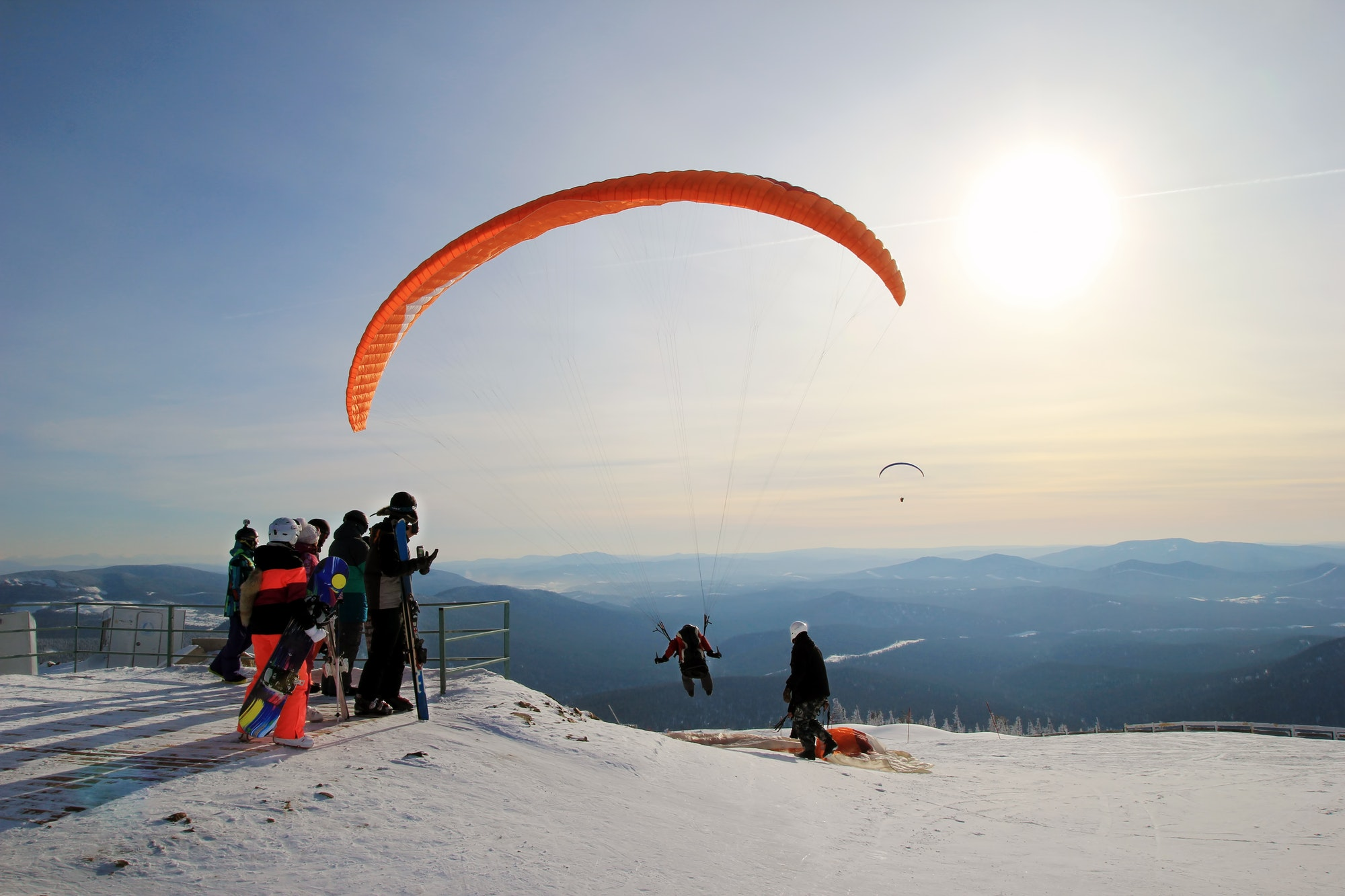 Travel to Sheregesh, Russia. Paraglider is taking off near to mountains. Winter landscape.