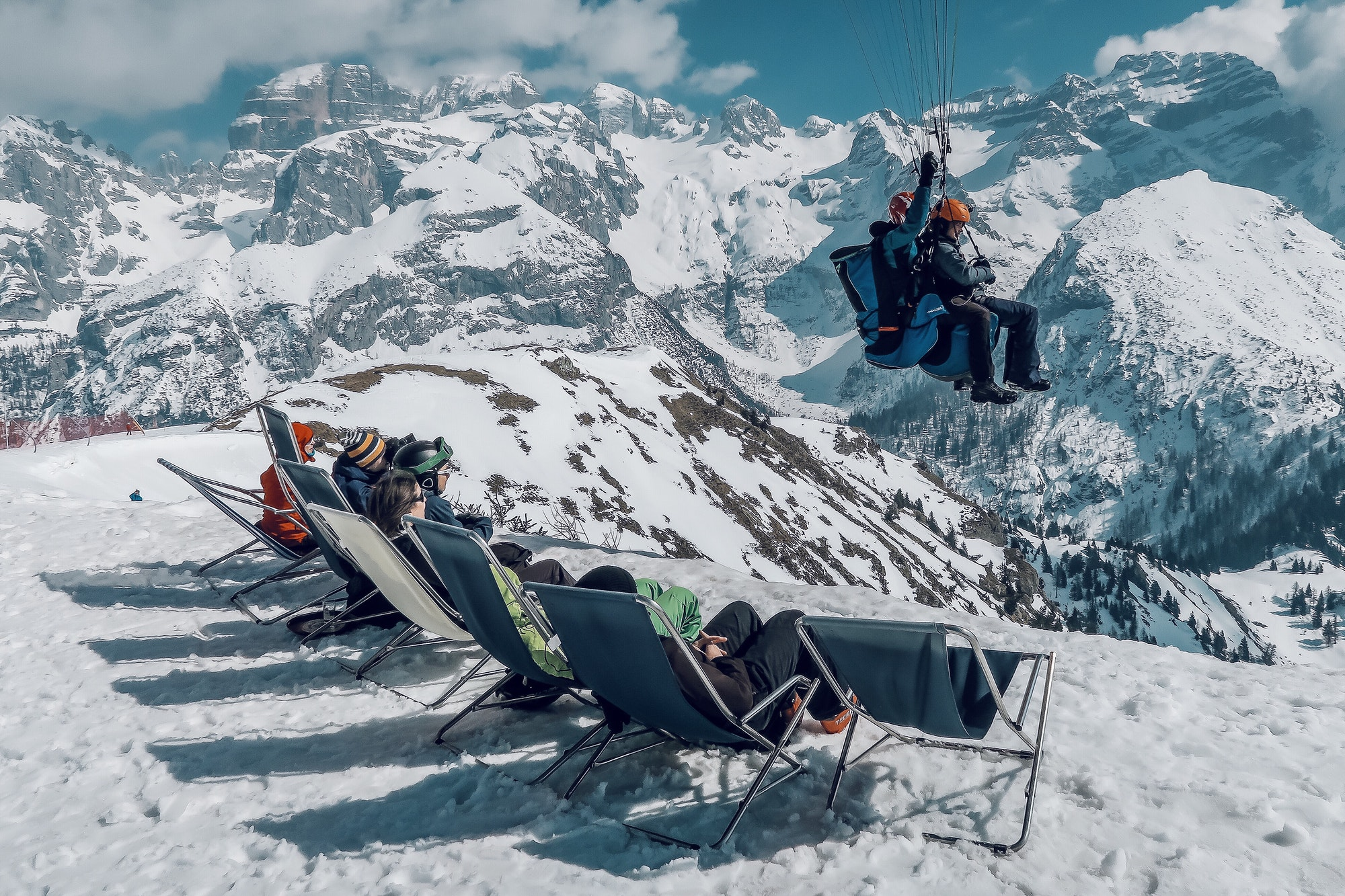 Unexpected paragliders fly over people relaxing in the winter sun in high mountains scenery.